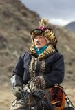 Kazakh eagle hunter traveling on his horse in a landscape of altai Mountains stock image