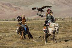 Kazakh Eagle Hunters traditional clothing, while hunting to the hare holding a golden eagles on his arms in desert mountain Stock Photos