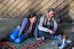 Kazakh family of hunters with golden eagles inside the mongolian Yurt. Stock Images