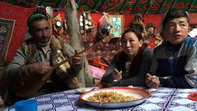 Kazakh family of hunters with golden eagles inside the mongolian Yurt.