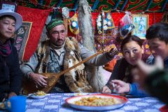 Kazakh family of hunters with golden eagles inside the mongolian Yurt. Royalty Free Stock Photos