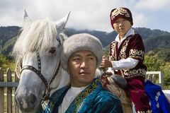 Kazakh father and son on his horse in traditional dresses at kazakh show of national games. Father and son from Kazakhstan with the boy sitting on the horse Royalty Free Stock Images