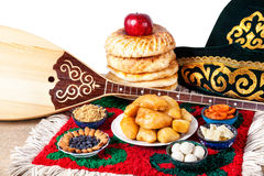 Kazakh food, dombra and hat. Asian dishes and Dombra Kazakh instrument on the ethnic carpet in yurta Royalty Free Stock Photos