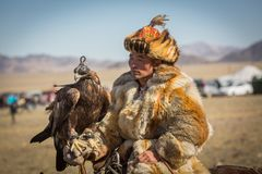 Kazakh Golden Eagle Hunter at traditional clothing, during annual national competition with birds of prey `Berkutchi` Stock Images