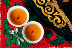 Kazakh hospitality. Kazakh national hat and black tea in two teabowls on the ethnic red carpet with oriental green pattern Royalty Free Stock Photo