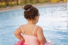 Kazakh little girl playing near swimming pool. Pretty little kazakh curly girl playing by the swimming pool Stock Image