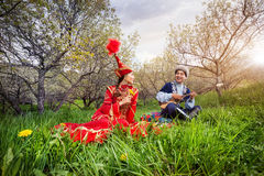 Kazakh love song. Kazakh men playing dombra and singing the song for women in red on the green grass in Almaty, Kazakhstan, Central Asia Royalty Free Stock Image