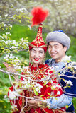 Kazakh love in Spring. Happy couple in Kazakh costumes in Spring Blooming apple garden of Almaty, Kazakhstan, Central Asia Stock Images