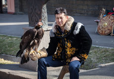 Kazakh man with falcon. ALMATY, KAZAKHSTAN - MARCH 22, 2015: Man in national Kazakh costume holding falcon big bird with eyes closed by hat at Nauryz celebration Stock Image