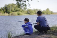 Kazakh man and his son are sitting and fishing on a lake shore in mid-summer royalty free stock photo