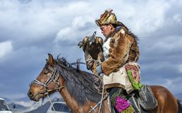Kazakh man in traditional outfit with his eagle on a horse royalty free stock photos