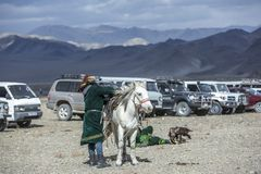 Kazakh man in traditional outfit with his horse stock photo