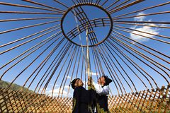 Builiding a nomadic yurt, in Kazakhstan. Kazakh men build a yurt and hold the crown of the dome in Saty Village, Kazakhstan Royalty Free Stock Photo
