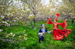 Kazakh music and dancing. Kazakh women dancing in red dress and men playing dombra at Spring Blooming garden in Almaty, Kazakhstan, Central Asia Royalty Free Stock Images