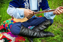 Kazakh music. Man in traditional Kazakh costume playing dombra instrument on the green grass in apple garden of Almaty, Kazakhstan, Central Asia stock images