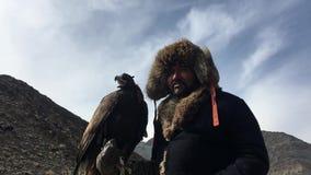 Kazakh traditionele kleding van Eagle Hunter, terwijl het jacht aan de hazen die een gouden adelaar op zijn wapen houden stock video