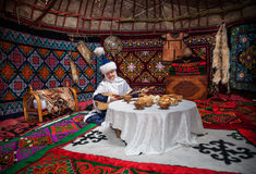 Kazakh women with dombra in the yurt. ALMATY, KAZAKHSTAN - MARCH 22, 2015: Woman in national Kazakh costume with dombra music instrument near the table with Royalty Free Stock Image