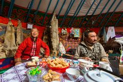 Kazakhs family of hunters with hunting golden eagles inside their the mongolian Yurts. Royalty Free Stock Photos