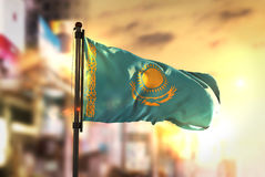Kazakhstan Flag Against City Blurred Background At Sunrise Backl Stock Image
