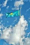 Kazakhstan flag on the background of sky. Royalty Free Stock Photo