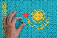 Kazakhstan flag is depicted on a puzzle, which the man`s hand completes to fold.  royalty free illustration