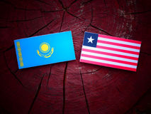 Kazakhstan flag with Liberian flag on a tree stump isolated. Kazakhstan flag with Liberian flag on a tree stump Royalty Free Stock Image