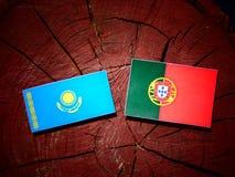 Kazakhstan flag with Portuguese flag on a tree stump isolated. Kazakhstan flag with Portuguese flag on a tree stump stock illustration