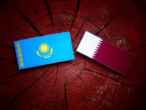 Kazakhstan flag with Qatari flag on a tree stump isolated. Kazakhstan flag with Qatari flag on a tree stump Stock Images