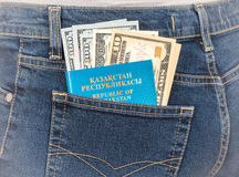 Kazakhstan passport and dollar bills in the back jeans pocket Royalty Free Stock Photo