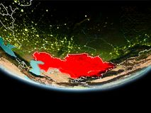 Kazakhstan in red in the evening. Country of Kazakhstan in red on planet Earth in the evening with visible border lines and city lights. 3D illustration Royalty Free Stock Image