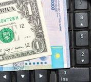 Kazakhtenge och dollar på ett bärbar datortangentbord Arkivbild
