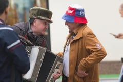 KAZAN, ΡΩΣΙΑ - 21 ΙΟΥΝΊΟΥ 2018: Ηλικιωμένος αρσενικός μουσικός οδών ακορντεονιστών που μιλά με το εύθυμο ώριμο άτομο πομπών Στοκ Εικόνα