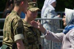 KAZAN, RÚSSIA - 23 DE JUNHO DE 2018: Festival Tatar tradicional Sabantuy - mulher adulta bonito em um lenço que fala aos soldados fotos de stock