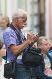 KAZAN, RÚSSIA - 21 DE JUNHO DE 2018: O fotógrafo profissional do homem maduro que está na rua de Bauman e usa um smartphone Imagem de Stock Royalty Free