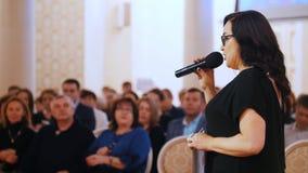 Kazan, Rússia 30-03-2019: Povos que sentam-se no salão e que esperam o desempenho Uma mulher que lê o discurso vídeos de arquivo