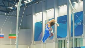 Kazan Rosja, Kwiecień, - 18, 2018: Młoda męska gimnastyczka wykonuje na gimnastycznych pierścionkach zdjęcie wideo