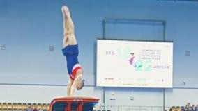 Kazan Rosja, Kwiecień, - 18, 2018: Młoda sportowa męska gimnastyczka wykonuje skok przy rywalizacją zbiory