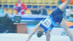 KAZAN ROSJA, KWIECIEŃ, - 18, 2018: rosjanin gimnastyk mistrzostwo - Młoda męska gimnastyczka przeskakuje na sądzie zdjęcie wideo