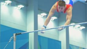 KAZAN ROSJA, KWIECIEŃ, - 18, 2018: rosjanin gimnastyk mistrzostwo - Sportowy męski gimnastyczki doskakiwanie na barze zdjęcie wideo
