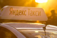 KAZAN, RUSLAND - JUNI 21, 2018: - Bovenkant van auto met identificatielichten met embleem van Yandex-taxi bij de zomerzonsonderga Royalty-vrije Stock Foto's