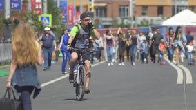 KAZAN, RUSLAND - JUNI 16, 2018: De Wereldbeker van FIFA - Menigte van mensen die onderaan de straat, twee mensen lopen die fiets  stock video