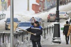 KAZAN, RUSSIA - febbraio 2018: Lavoratore che rimuove neve dalla via con una pala di legno fotografia stock libera da diritti
