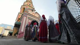 Kazan, Russia, 19 july 2017, Folklore ensemble in russian national costumes visits Orthodox church. Wide angle stock footage