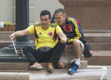 KAZAN, RUSSIA - JUNE 21, 2018: FIFA World Cup - Male Iranian football fans makes selfie sitting on the stairs at the. Street, close up Stock Photography