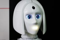 White personal robot looks like a human.Beautiful cyborg female face on the dark black background stock photo