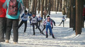 KAZAN, RUSSIA - MARCH, 2018: Young sportsmans running on ski-track at the ski competition. In the park, slow motion stock video