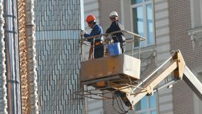Kazan, Russia - 15 september 2017 - Two Men Workers in Truck Tower are repairing fassade of building stock video footage