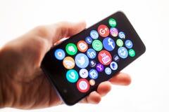 KAZAN RYSSLAND - NOVEMBER 22, 2017: Mannens hand rymmer en smartphone med sociala massmediasymboler arkivfoton