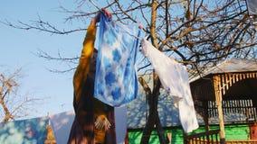Woman in yellow hangs clean towel on rope in house yard