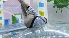 Little boy plays on large clear ball in modern playroom backside view. Kazan, Tatarstan Russia - August 24 2018: Backside view little boy plays and rests on stock video